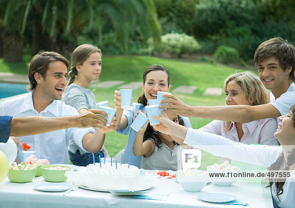 Familie klirrende Tassen über Geburtstagskuchen