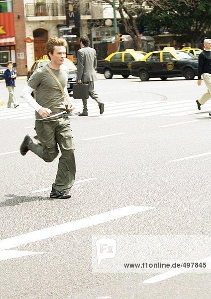 Junger Mann rennt über die Stadtstraße