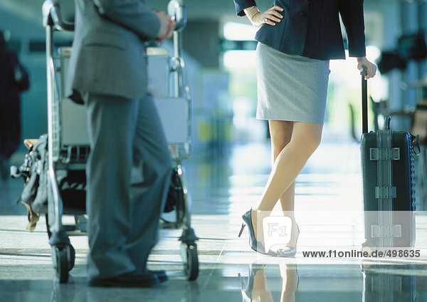 Geschäftsmann und Geschäftsfrau stehend mit Gepäck am Flughafen