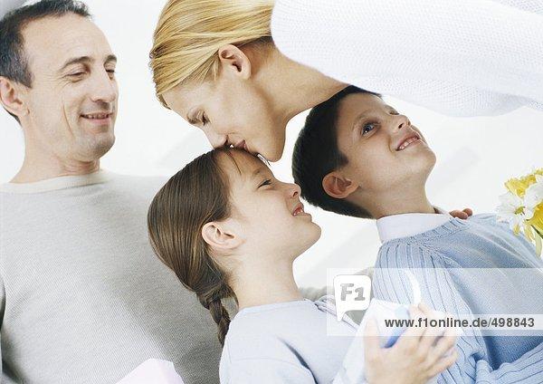 Familienszene  Mutter küsst Tochter auf den Kopf