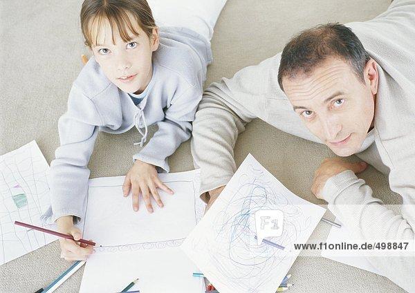 Mann und Tochter liegen auf dem Boden und zeichnen zusammen
