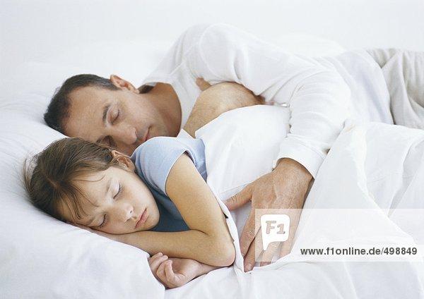 Mann neben Tochter im Bett liegend