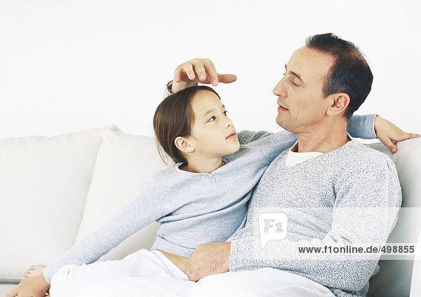 Mann und Tochter sitzen zusammen auf dem Sofa.