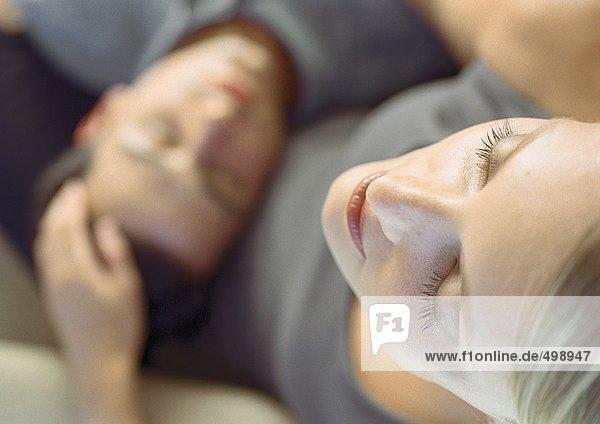 Mann schläft mit Kopf im Schoß der Frau