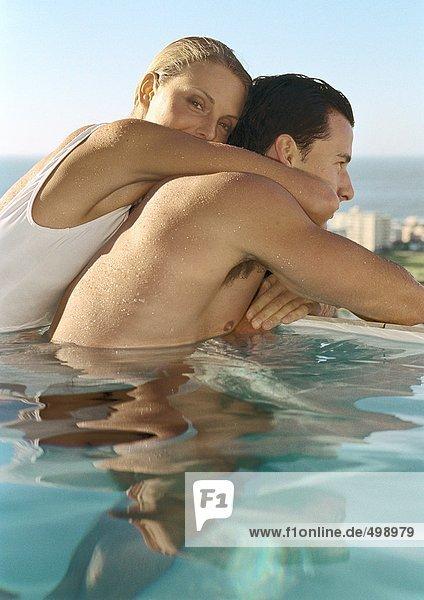Frau umarmt Mann im Pool