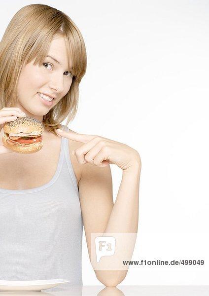 Frau hält sich hoch und zeigt auf Sandwich