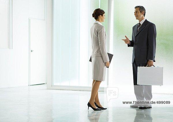 Geschäftsmann und Geschäftsfrau im Gespräch in der Lobby