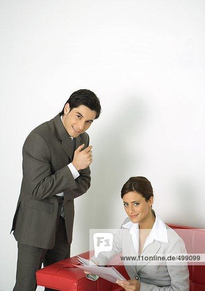 Geschäftsmann neben Geschäftsfrau auf Sofa sitzend  beide lächelnd