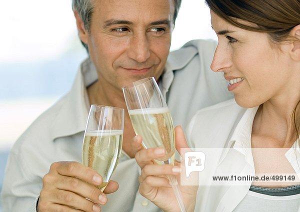 Ein paar klirrende Gläser Champagner und lächeln sich an.