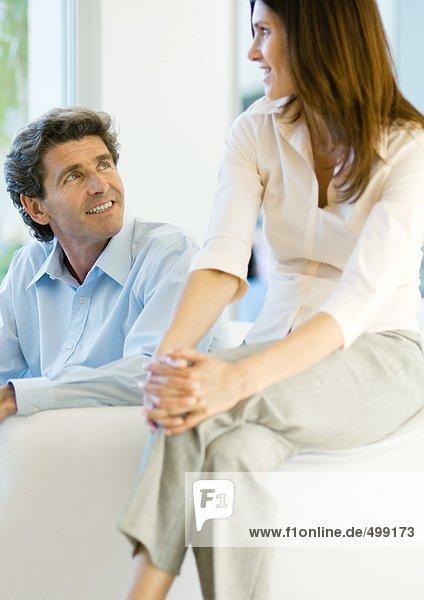 Mann sitzt auf dem Sofa  während die Frau auf dem Arm sitzt.