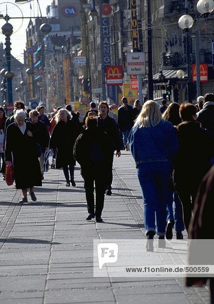 Menschenmenge  die an einem kalten Tag den Bürgersteig hinuntergeht  Gebäude im Hintergrund.