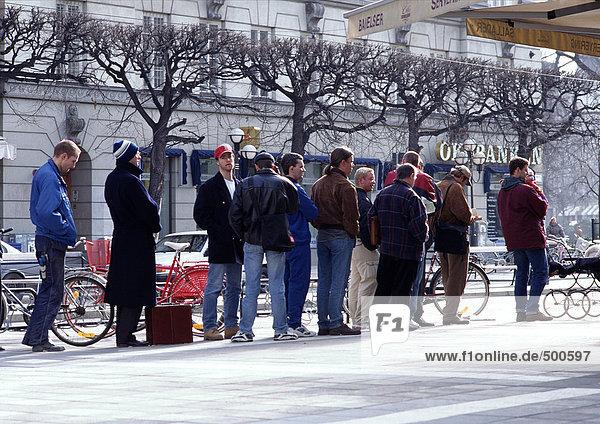 Gruppe von Leuten  die für kaltes Wetter gekleidet sind und auf dem Bürgersteig Schlange stehen.
