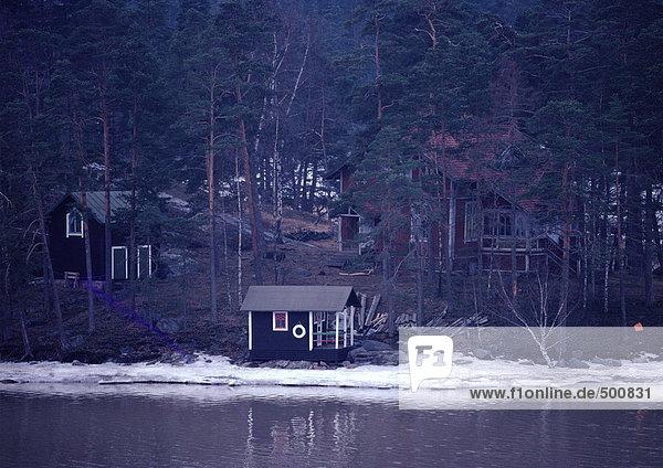 Schweden  Hütten im Wald am Rande des Wassers