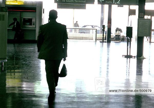 Man walking through train station  silhouette.