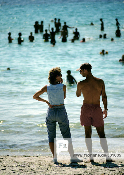 Leute stehen am Strand  Leute spielen im Wasser im Hintergrund  Rückansicht.