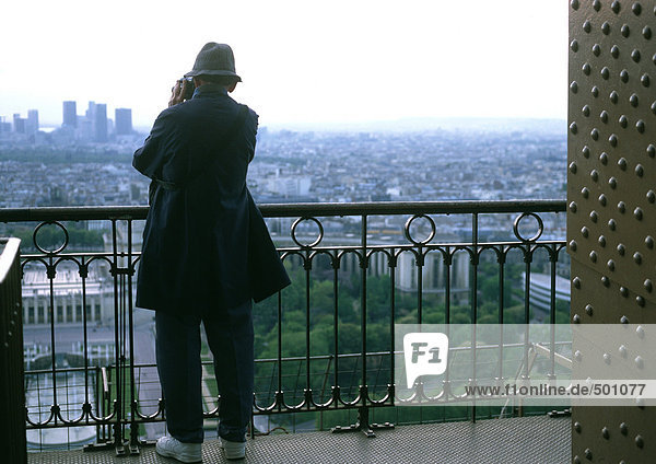 Mann fotografiert vom Balkon aus  Rückansicht.