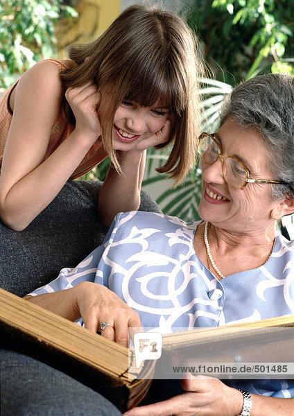 Girl looking over senior's shoulder at book.