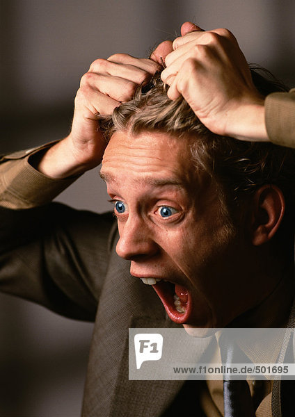 Man with mouth and eyes wide open  pulling hair  close-up