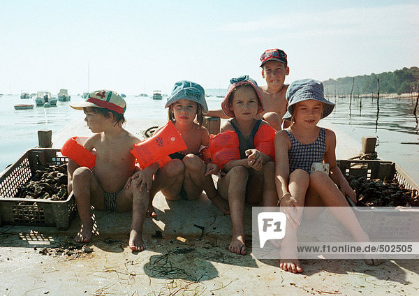 Children sitting lined up  wearing water wings  on beach