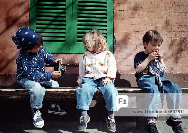 Kinder sitzen auf der Bank