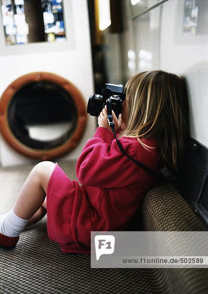 Kleines Mädchen auf Sofa mit Kamera