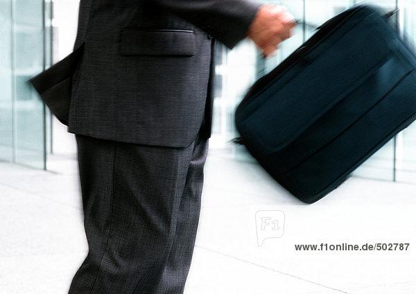 Mann hält Tasche  Mittelteil  verschwommene Bewegung