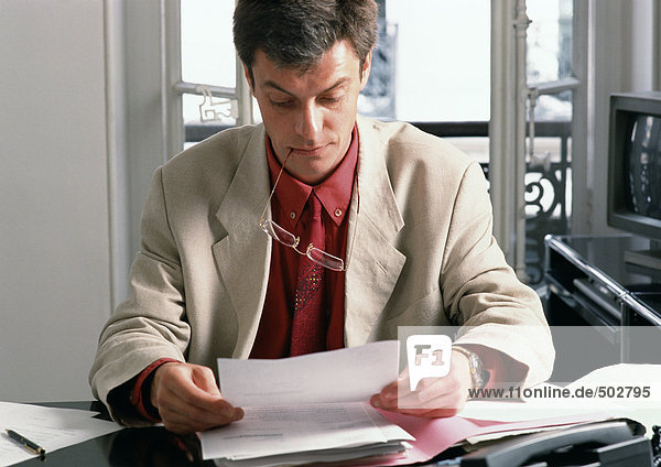 Man sitting at desk holding glasses in mouth  reading document