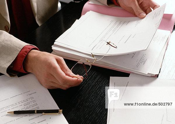 Hände halten Brille und Dokument