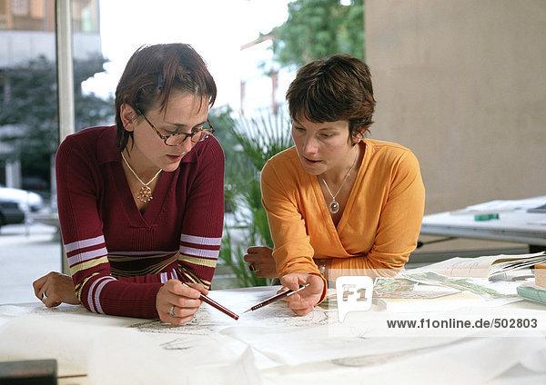 Zwei Frauen  die sich auf den Tisch lehnen und Stifte halten.