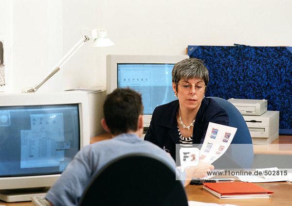 Mann hält Dokument an Frau im Amt aus