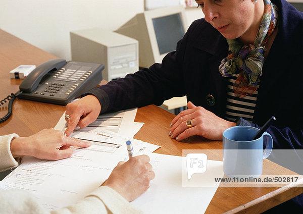 Zwei Personen sitzen sich am Tisch gegenüber und sehen sich das Dokument an.