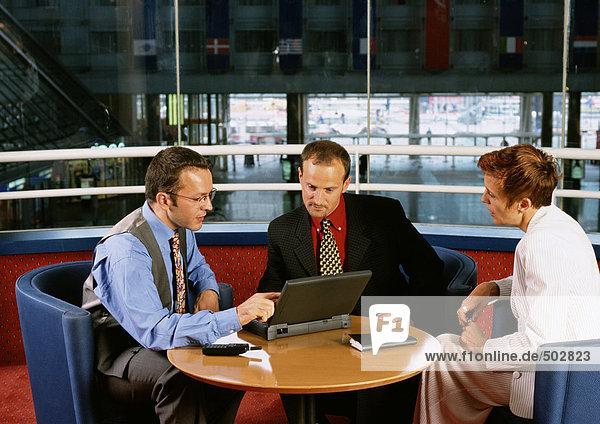 Zwei Männer und eine Frau sitzen am Tisch und schauen auf den Laptop.
