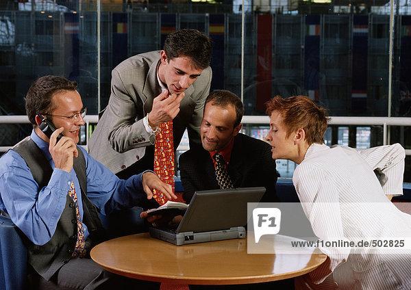 Drei Männer und eine Frau sitzen am Tisch und schauen auf den Laptop.