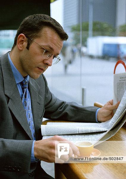 Mann beim Kaffeetrinken beim Zeitungslesen