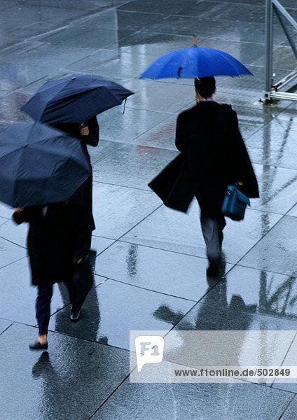 Drei Personen halten Regenschirme in der Straße  hohe Blickwinkel