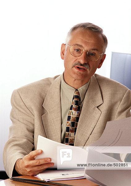 Mann am Schreibtisch sitzend  Dokument haltend