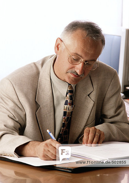 Mann am Schreibtisch sitzend  schreibend