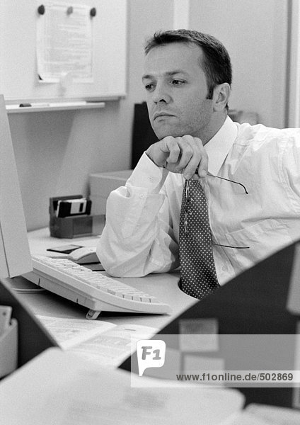 Mann am Schreibtisch sitzend  Ellenbogen auf Tisch  s/w