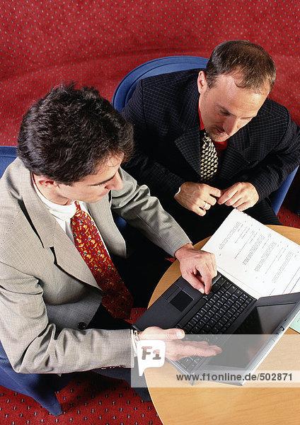 Zwei Männer sitzen am Tisch und schauen auf den Laptop.