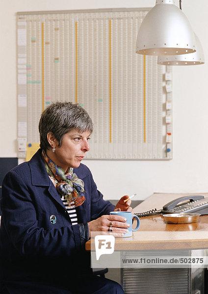 Frau am Tisch sitzend  Tasse haltend und Zigarette rauchend