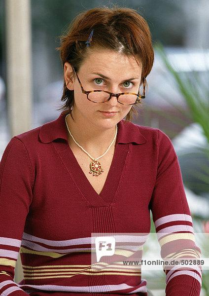 Frau schaut über den Brillenrand  Portrait