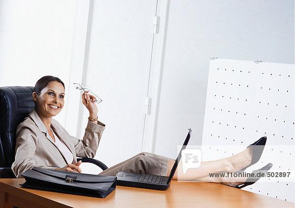 Geschäftsfrau am Schreibtisch sitzend mit Füßen auf dem Tisch  lächelnd