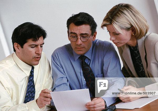 Zwei Geschäftsleute und eine Geschäftsfrau  die das Dokument prüft.