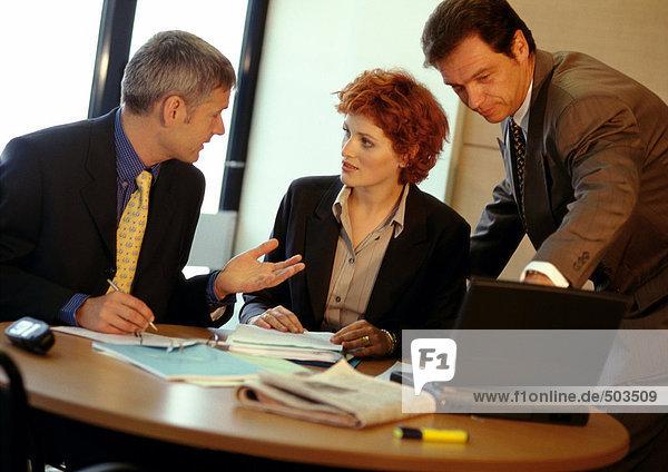 Zwei Geschäftsleute und eine Geschäftsfrau am Tisch  einer davon mit Laptop