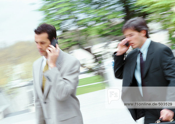 Two businessmen walking outside  holding cell phones  blurred