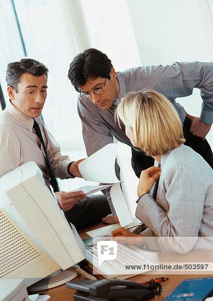 Zwei Geschäftsleute und eine Geschäftsfrau bei der Prüfung von Dokumenten