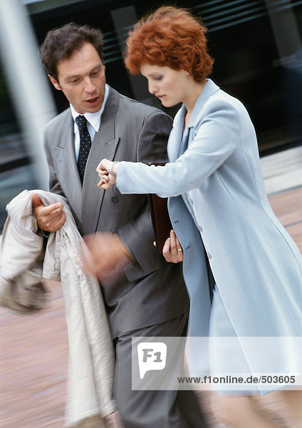 Businessman and businesswoman walking side by side outside  businesswoman looking at watch