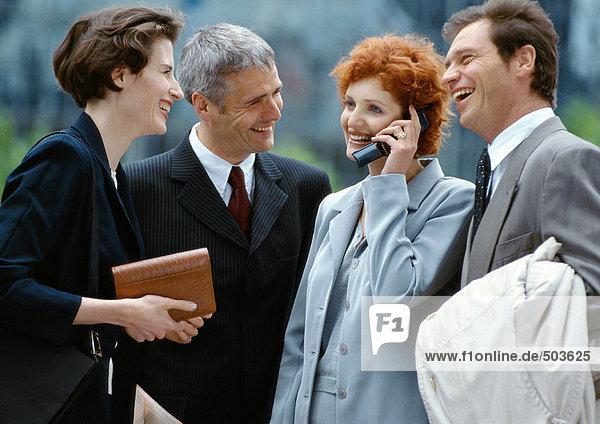 Vier Geschäftsleute stehen draußen lächelnd  Geschäftsfrau am Handy