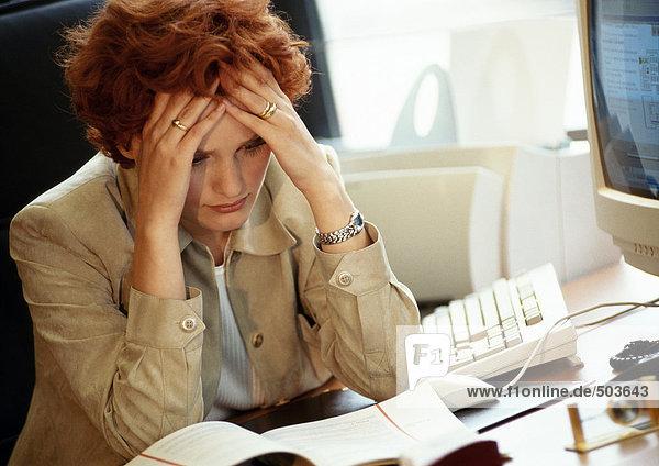 Geschäftsfrau am Schreibtisch sitzend  Hände auf dem Kopf