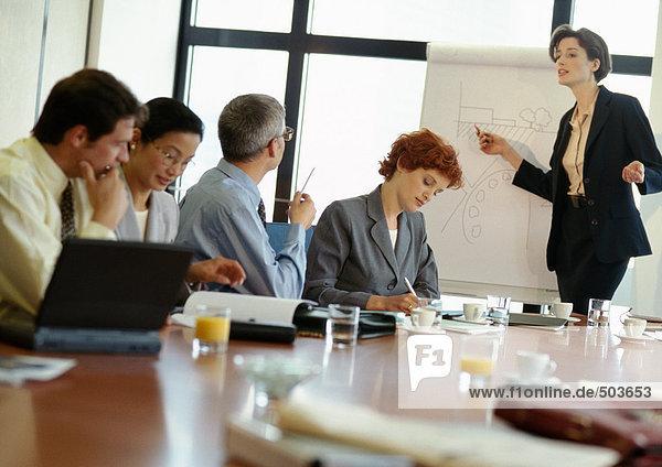 Gruppe von Geschäftsleuten im Konferenzraum  Geschäftsfrau zeigt auf Präsentationstafel